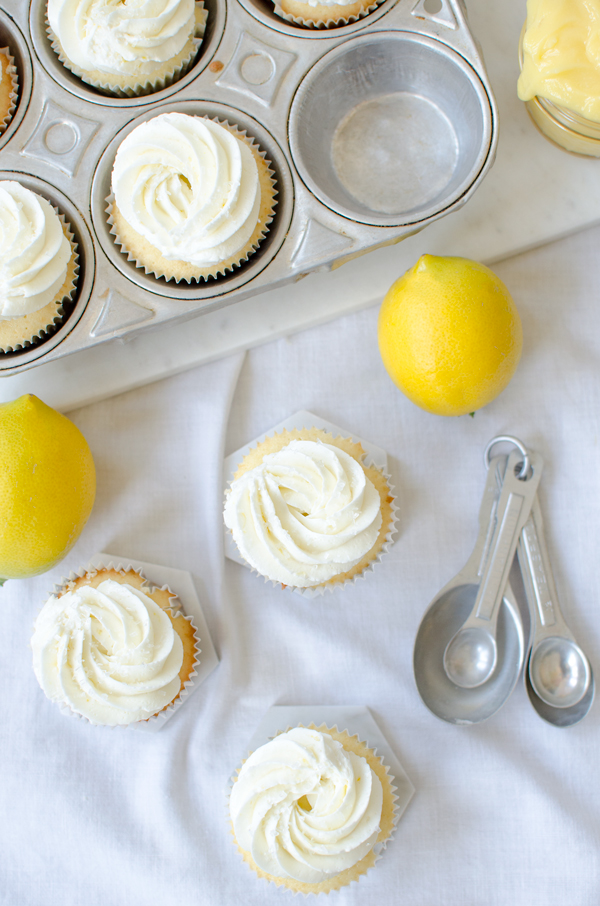 An easy but impressive cupcake - vanilla cupcakes filled with lemon curd and topped with lemon buttercream frosting!