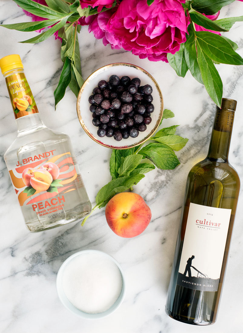 Boozy Peach Sangria Popsicles Served in Prosecco Recipe - perfect to beat the summer heat!